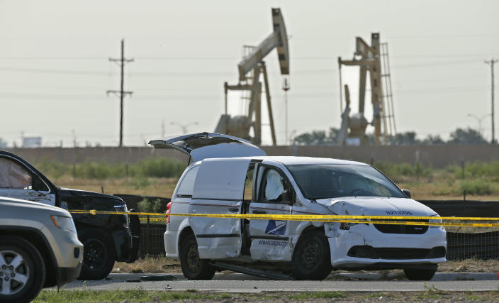A U.S. Mail vehicle, right, which was involved in Saturday's shooting, is pictured outside the Cinergy entertainment center Sunday, Sept. 1, 2019, in Odessa, Texas. The death toll in the West Texas shooting rampage increased Sunday as authorities investigated why a man stopped by state troopers for failing to signal a left turn opened fire on them and fled, shooting over a dozen people as he drove before being killed by officers outside a movie theater. A police vehicle is partially blocked at left. (AP Photo/Sue Ogrocki)