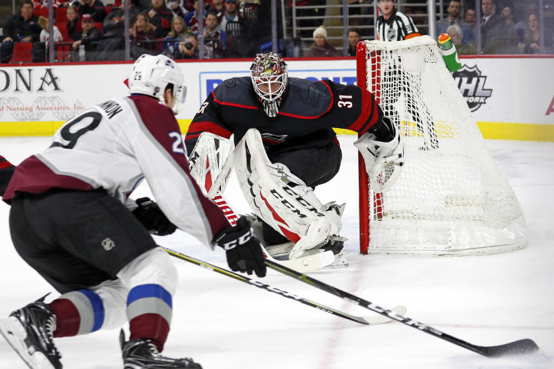 Carolina Hurricanes goaltender Anton Forsberg (31), of Sweden, eyes the puck as Colorado Avalanche's Nathan MacKinnon (29) skates with it during the first period of an NHL hockey game in Raleigh, N.C., Friday, Feb. 28, 2020. (AP Photo/Karl B DeBlaker)