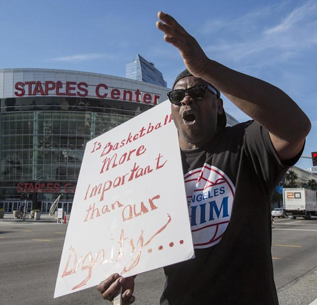 Jerry Carr carries a sign in protest of Los Angeles Clippers owner Donald Sterling, outside Staples Center on Tuesday, April 29, 2014, in Los Angeles, before Game 5 of an opening-round NBA basketball playoff series between the Clippers and the Golden State Warriors. NBA Commissioner Adam Silver announced Tuesday that Sterling has been banned for life by the league for making racist comments that hurt the league. (AP Photo/Ringo H.W. Chiu)