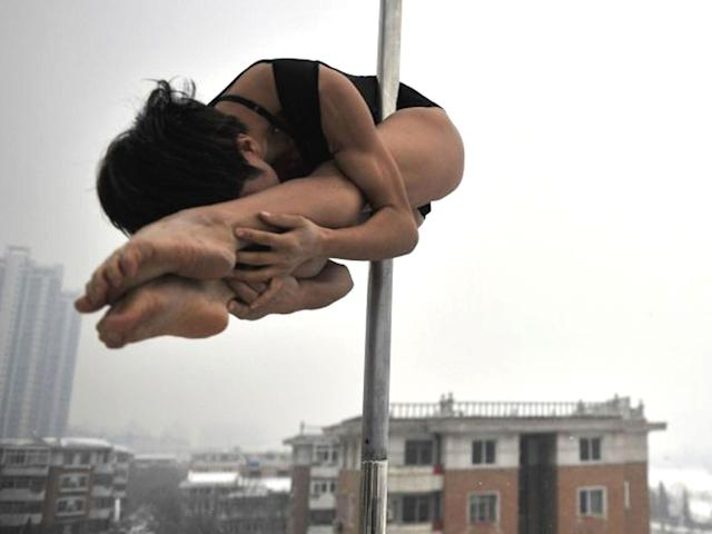 A pole dancer practices during a promotional event by members of China's national pole dancing team: Getty Images