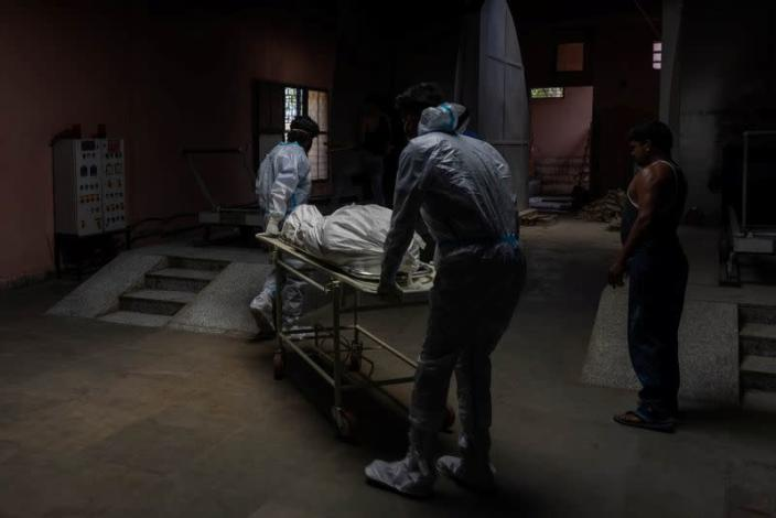 Health workers carry the body of a person, who died from complications related to the coronavirus disease (COVID-19), for cremation at a crematorium in New Delhi
