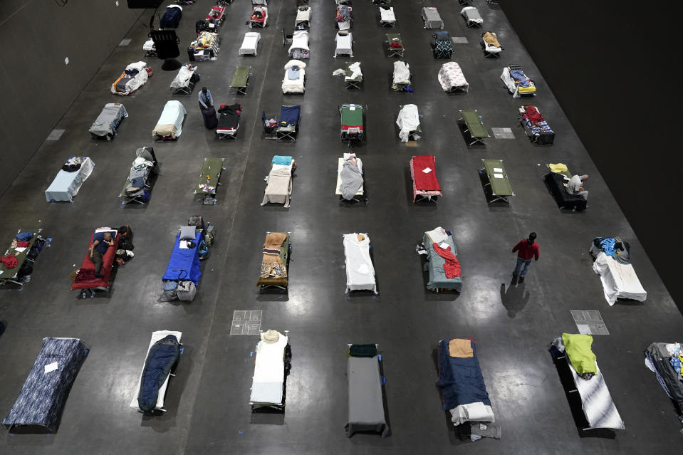 "FILE - In this Aug. 11, 2020, file photo, beds fill a homeless shelter inside the San Diego Convention Center in San Diego. A coalition in California is proposing legislation to boost taxes on wealthy multi-national corporations to raise more than $2 billion a year to end homelessness. Supporters say Assembly Bill 71, if approved, would ""reinvent"" the state's approach to solving homelessness. (AP Photo/Gregory Bull, File)"