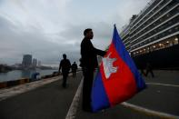 A man holds a Camboadian flag as MS Westerdam, a cruise ship that spent two weeks at sea after being turned away by five countries over fears that someone aboard might have the coronavirus, docks in Sihanoukville