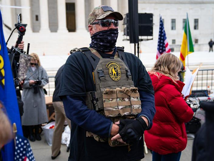Man in camouflage, a bulletproof vest and sunglasses stands guard with hands folded