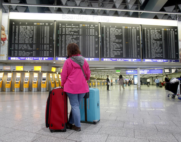 A passenger stands in the terminal at the Frankfurt airport as Lufthansa pilots went on a three-day strike in Frankfurt, Germany, Wednesday, April 2, 2014. Germany's Lufthansa said it has canceled almost 900 domestic and intercontinental flights on the first day of a three-day strike by the pilots' union. Airline spokeswoman Barbara Schaedler said that up to 900 flights were canceled for Wednesday and that it expects to cancel about 3,800 flights altogether, affecting more than 425,000 passengers. (AP Photo/Michael Probst)
