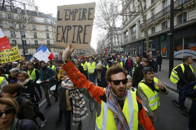 A protester holds a placard reads in French ''Empire expires'' during a rally in Paris, Saturday, March 23, 2019. Yellow vest demonstrators gathered in Paris and other French cities for a 19th round of demonstrations as authorities issued bans on protests in certain areas and enhanced security measures in an effort to avoid a repeat of last week's riots in the capital. (AP Photo/Michel Euler)
