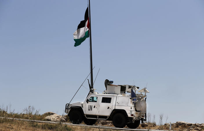 Spanish U.N peacekeepers pass under a Palestinian flag as they patrol on the Lebanese side of the Lebanese-Israeli border in the southern village of Kfar Kila, Lebanon, Saturday, May 15, 2021. On Israel's northern border with Lebanon, Israeli troops opened fire on Friday when a group of Lebanese and Palestinian protesters on the other side cut through the border fence and briefly crossed. (AP Photo/Hussein Malla)