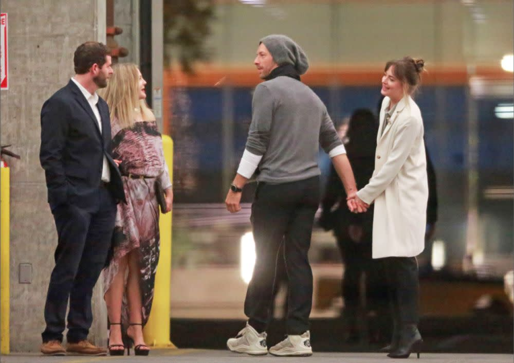 Dakota Johnson and Chris Martin speaking to Drew Barrymore (left)