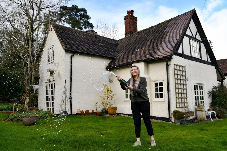 Jemma Nicklin, 23, celebrates with a bottle of champagne during her first visit to Shrubbery Farm in Longnor near Shrewsbury, a 300-year-old four bedroom farmhouse which she won after buying two £2 tickets in a raffle organised by owner Mike Chatha. Photo: Jacob King/PA via Getty Images