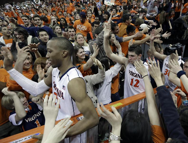 Virginia forward Akil Mitchell, front, and Joe Harris (12) are swarmed by fans as they celebrate their win over Syracuse after an NCAA College basketball game in Charlottesville, Va., Saturday, March 1, 2014. Virginia won the game 75-56. (AP Photo/Steve Helber)