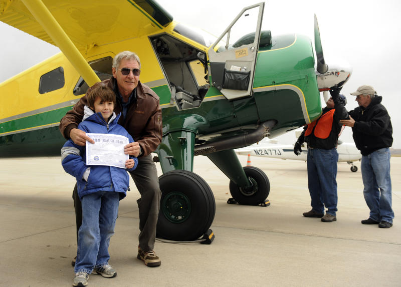 Actor Harrison Ford visits Denver and gives some kids an airplane ride from Centennial Airport. Sean Keeney, 8, of Littleton gets his photo taken with Ford after his plane ride. For Bill Husted column. Kathryn Scott Osler, The Denver Post (Photo By Kathryn Scott Osler/The Denver Post via Getty Images)