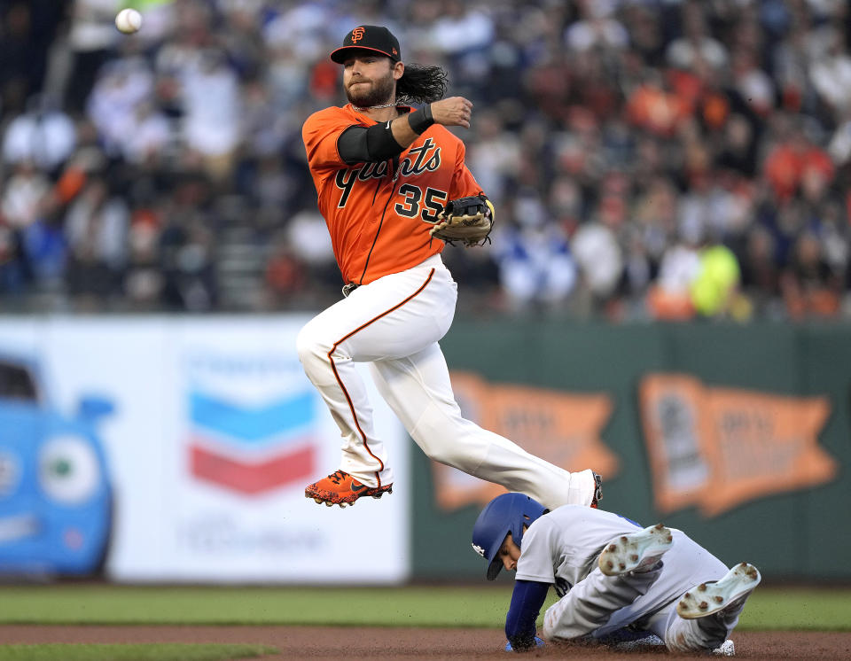 SAN FRANCISCO, CALIFORNIA - SEPTEMBER 03: Brandon Crawford #35 of the San Francisco Giants throws to first base while leaping over Trea Turner #6 of the Los Angeles Dodgers in the top of the first inning at Oracle Park on September 03, 2021 in San Francisco, California. The throw was not in time to get Max Muncy #13. (Photo by Thearon W. Henderson/Getty Images)