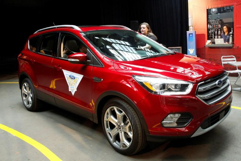 "Guests are served coffee while riding in a 2017 Ford Escape SUV during Ford's ""Escape the Room"" drive experience in New York"