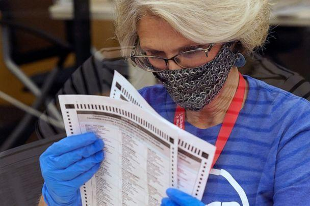 PHOTO: Gerri Kanelos inspects a ballot for damage before they are sent to be tabulated at the Sacramento County Registrar of Voters Office in Sacramento, Calif., Tuesday, Sept. 14, 2021. (Rich Pedroncelli/AP)
