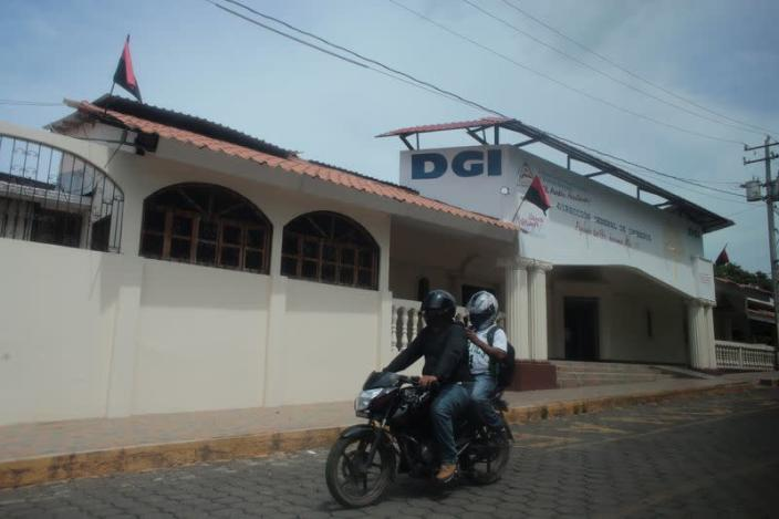 FILE PHOTO: Men ride on a motorcycle past an office of the Nicaraguan tax authority (DGI), in Managua