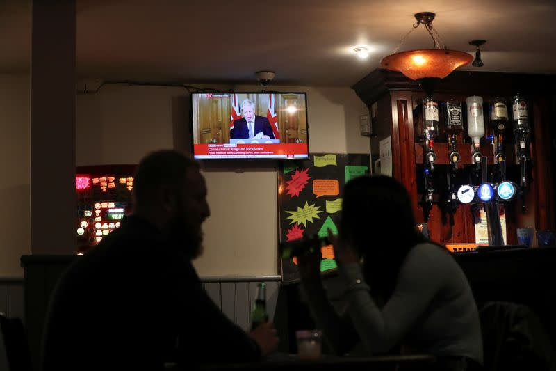 People talk inside a pub as Britain's Prime Minister Boris Johnson speaks at a news conference, in Durham