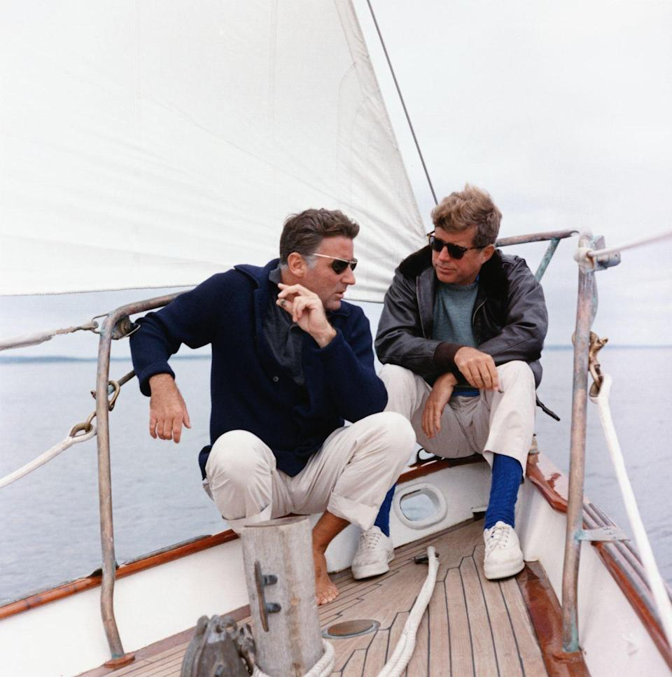 "<p>President Kennedy with his brother-in-law Peter Lawford sit aboard the ""Manitou,"" a yacht donated to the U.S. Coast Guard that later became known as the ""Floating White House."" </p>"