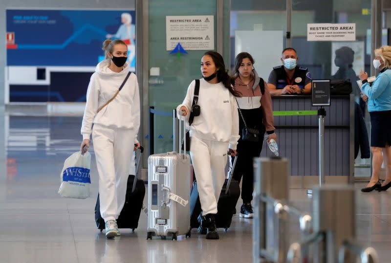 Tourists walk with their luggage as they arrive at Malaga-Costa del Sol Airport, in Malaga