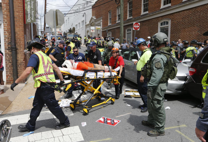 Rescue personnel help injured people after a car ran into a large group of protesters during a white nationalist rally in Charlottesville, Va., Saturday, Aug. 12, 2017. The nationalists were holding the rally to protest plans by the city of Charlottesville to remove a statue of Confederate Gen. Robert E. Lee. There were several hundred protesters marching in a long line when the car drove into a group of them. (AP Photo/Steve Helber)