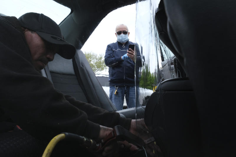 Luis Hidalgo, right, watches as Joel Rios installs a plastic barrier in his car to protect himself and his passengers from the new coronavirus in the Bronx borough of New York, Wednesday, May 6, 2020. Hidalgo, who drives sometimes for Uber, said he has not worked for two months for fear of the coronavirus but mounting bills have forced him back to work; he hopes the plastic barrier will keep him and his passengers safe. (AP Photo/Seth Wenig)