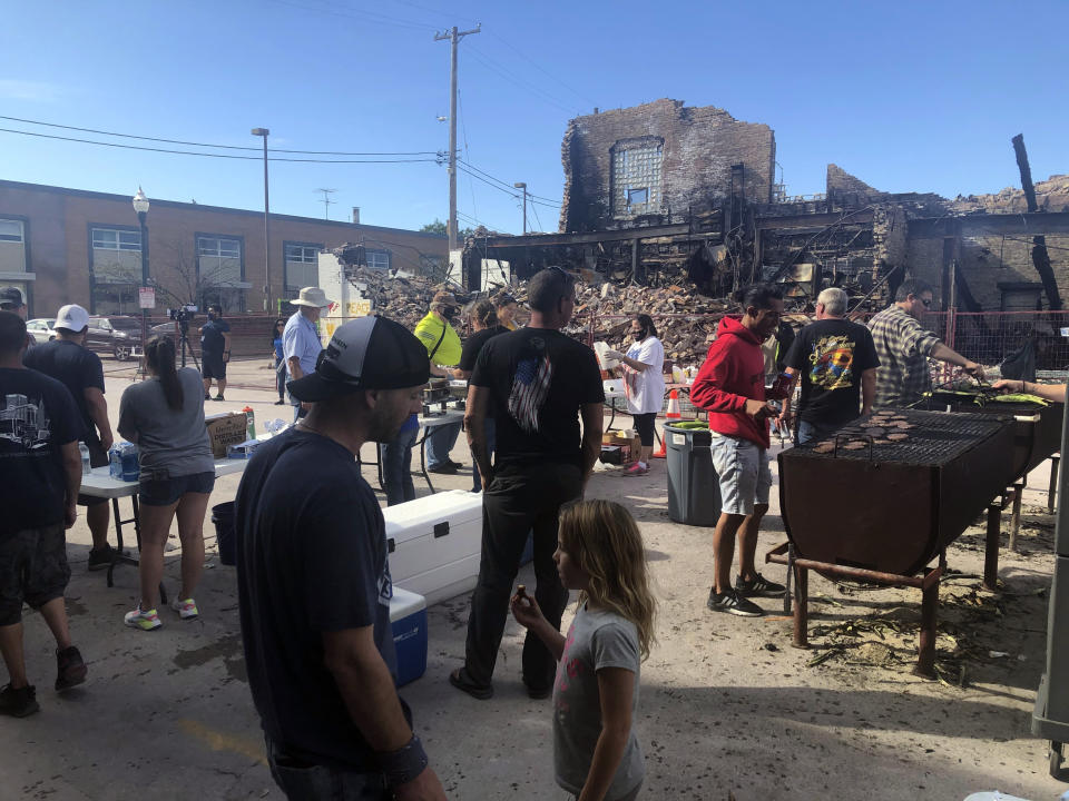 Volunteers prepare hamburgers for mural painting volunteers working in front of one of the city's dozens of burnt buildings in Kenosha, Wis., Sunday, Aug. 30, 2020. The southern Wisconsin city remained on edge following the police shooting of Jacob Blake, a Black man, and the violent protests that followed. (AP Photo/Russell Contreras)