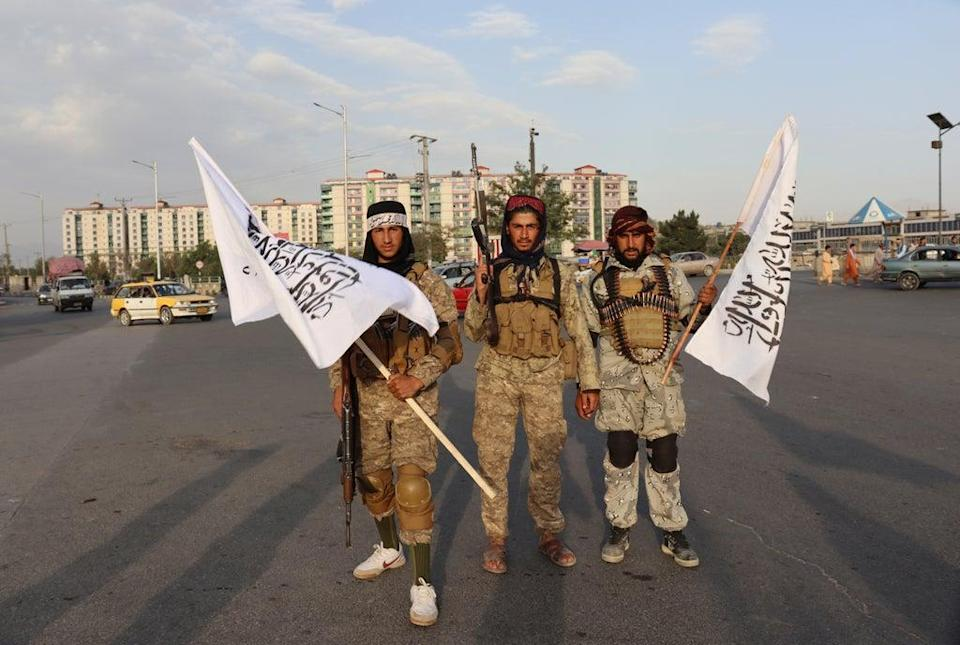 Taliban fighters celebrate with flags as they prepare for the last US flight to leave Kabul (AP Photo/Khwaja Tawfiq Sediqi) (AP)