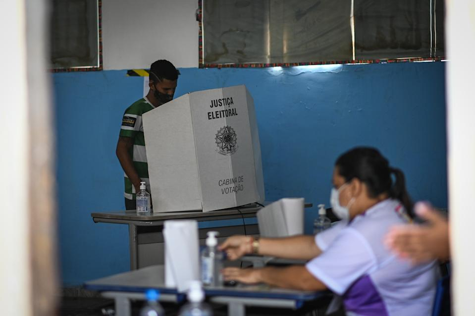 A man arrives to vote at a polling booth during municipal elections amid the Coronavirus (COVID-19) pandemic in Santana, Amapá State, Brazil, on November 15, 2020. The population of the Amapá state has been registering blackouts and electricity rationing for 13 days, since a fire destroyed a transformer in an Amapás energy substation. (Photo by Andre Borges/NurPhoto via Getty Images)