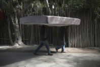 Workers carry a mattress from one hotel cabin to another in Tulum, Quintana Roo state, Mexico, Monday, Jan. 4, 2021. Tourism, which has been affected by the new coronavirus pandemic, accounts for 87% of Quintana Roo's gross domestic product, said state Tourism Secretary Marisol Vanegas. (AP Photo/Emilio Espejel)