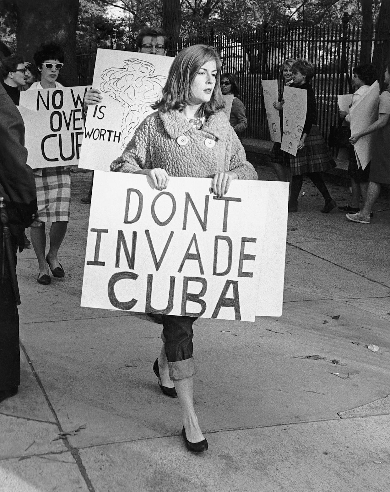 Picture shows people picketing outside of the White House in protest of the US involvement with Cuba. The woman in the foreground is holding a sign plainly stating her point, 'Don't invade Cuba'. Undated photo circa 1960s.