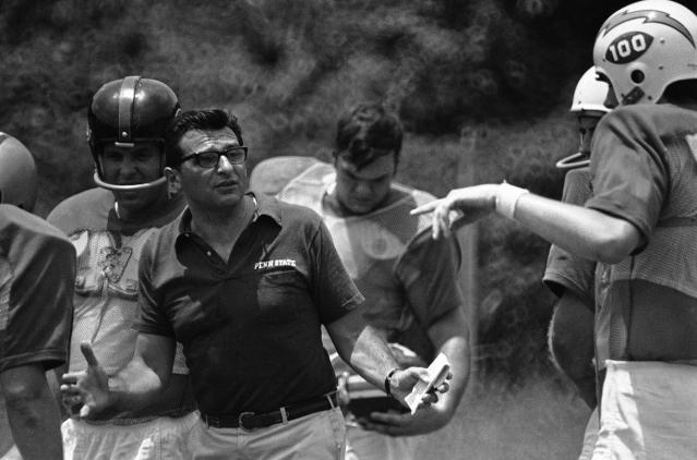 <p>Joe Paterno of Penn State, coach of the East All Stars, explains a play to quarterback Buster O'Brien, right, of Richmond, during Wednesday's practice session for the Coaches All-America football game, June 26, 1969, in Atlanta. (Photo: Charles Kelly/AP) </p>