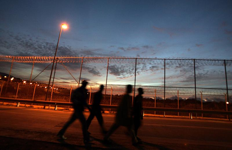 FILE -  In this Oct. 23, 2005 file photo, a group of African immigrants walk past the fence between Morocco and the Spanish enclave of Melilla. Spain says 160 migrants rushed fences guarding one of its north African enclaves on Monday Sept. 3, 2012 and the county's Foreign Minister Jose Manuel Garcia Margallo raised concerns more may swarm to Spanish islands just off Morocco's northern coast. Migrants tried to breach two sections of fences that act as a border between Melilla and Morocco early Monday, with about 10 succeeding in entering Spanish territory, officials said. Some 70 illegal immigrants reached the tiny uninhabited island of Isla de Tierra off Morocco, joining another 19 who reached the archipelago last Wednesday. (AP Photo/Emilio Morenatti, File)