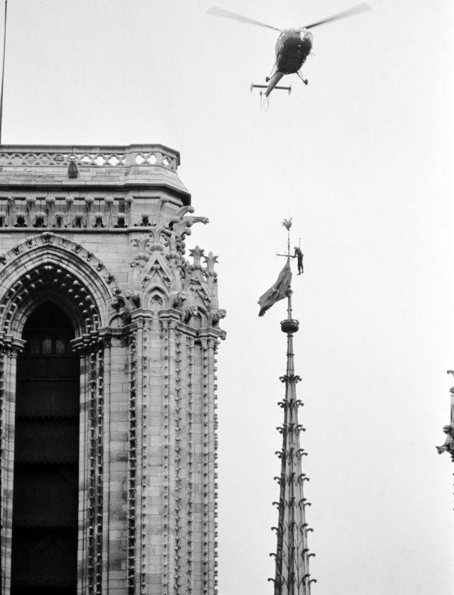 A Paris fire department helicopter hovers over Notre Dame Cathedral, in Paris, on Jan. 19, 1969, and lowers a fireman, dangling on the end of a line, to remove a blue and red South Vietnamese National Liberation Front, Viet Cong, flag placed on a 250-foot Cathedral spire.