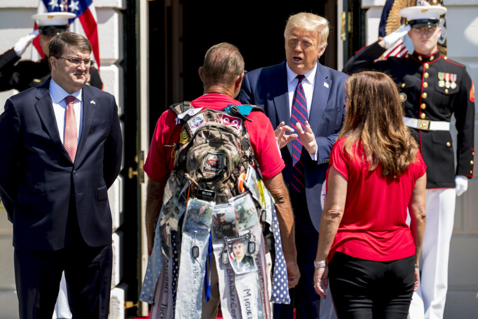 "President Donald Trump, accompanied by Veterans Affairs Secretary Robert Wilkie, left, and Karen Pence, the wife of Vice President Mike Pence, right, greets Terry Sharpe, center, known as the ""Walking Marine"" at the White House in Washington, Monday, July 27, 2020. Sharpe has walked from Summerfield, N.C., to Washington to raise awareness of the current veteran suicide rate. (AP Photo/Andrew Harnik)"