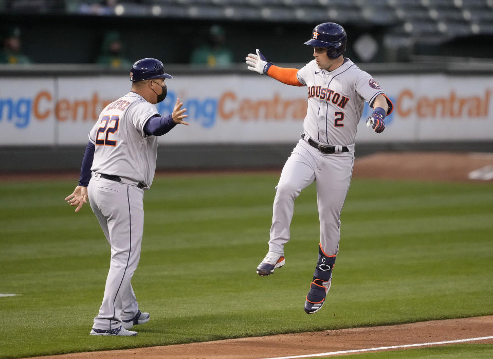 Houston Astros' Alex Bregman (2) celebrates with third base coach Omar Lopez (22) as he runs the bases after hitting a three-run home run against the Oakland Athletics during the third inning of a baseball game Friday, April 2, 2021, in Oakland, Calif. (AP Photo/Tony Avelar)
