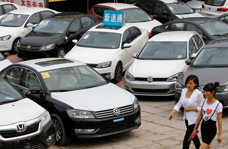 FILE PHOTO: Women walk past Volkswagen and Honda cars on display at an automobile market in Beijing
