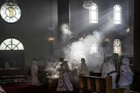 A priest wafts incense at the Bole Medhanialem Church in Addis Ababa, on June 20, 2021 during an early morning service as women congregate