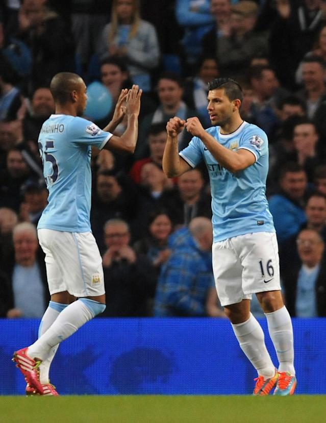 Manchester City's Sergio Aguero, right, celebrates after scoring against West Bromwich Albion with teammate Fernandinho during the English Premier League soccer match at the Etihad Stadium, Manchester, England, Monday April 21, 2014. (AP Photo/Rui Vieira)