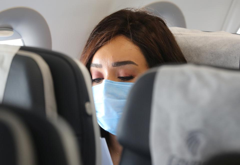 A traveller wears a protective face mask on a plane, following an outbreak of the coronavirus disease (COVID-19), at Cairo International Airport in Cairo, Egypt, June 18, 2020. REUTERS/Mohamed Abd El Ghany