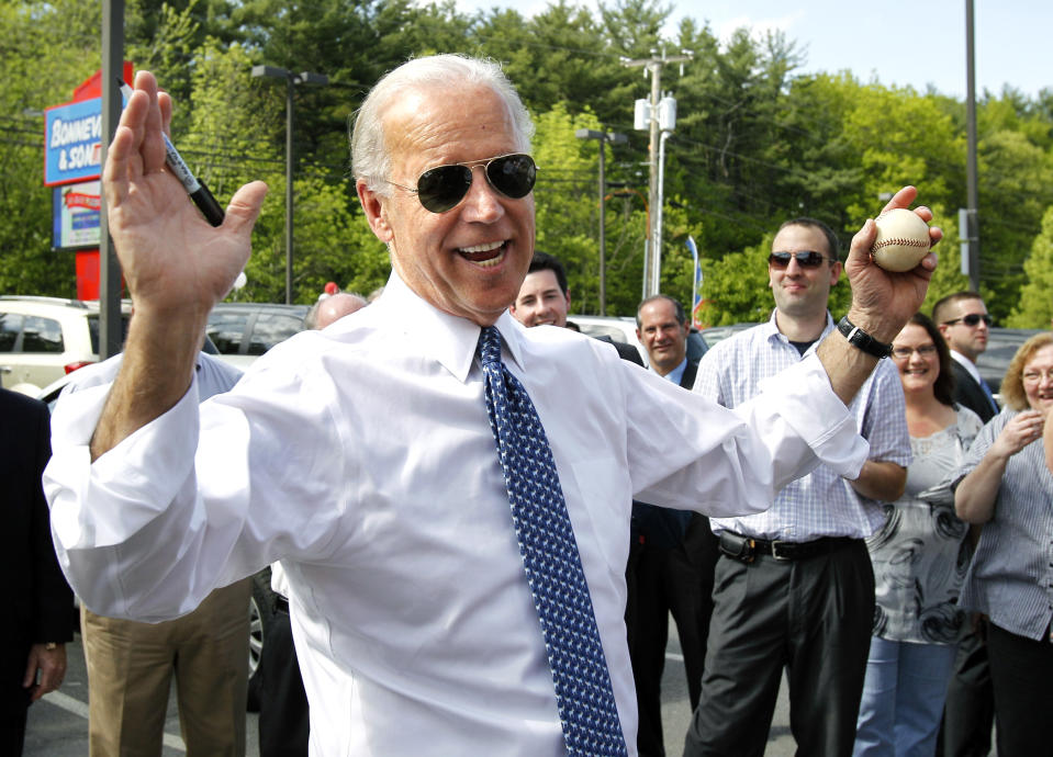Vice President Joe Biden jokes about the perils of throwing out a ceremonial first pitch as he autographs a baseball for a worker at Bonneville & Son's car dealership in Manchester, N.H., Wednesday, May 25, 2011. (AP Photo/Elise Amendola)