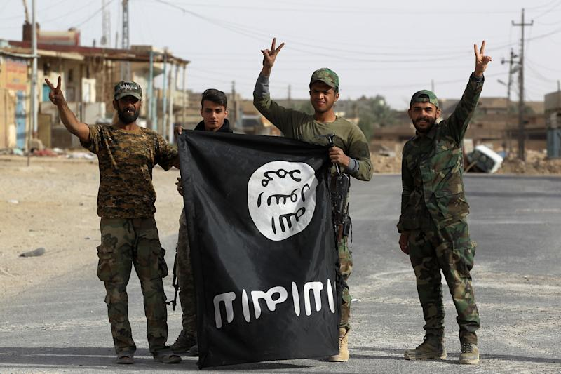 Iraqi members of the Hashed al-Shaabi (Popular Mobilisation units) carry an upsidedown Islamic State (IS) group flag in the city of al-Qaim, in Iraq's western Anbar province near the Syrian border as they fight against remnant pockets of Islamic State group jihadists on November 3, 2017. / AFP PHOTO / AHMAD AL-RUBAYE (Photo credit should read AHMAD AL-RUBAYE/AFP/Getty Images)