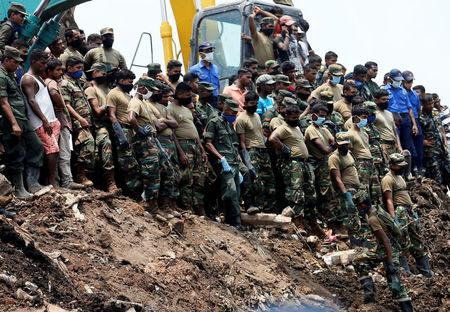 Members of the military wait until another rescue team recovers a dead victim during a rescue mission after a garbage dump collapsed and buried dozens of houses in Colombo