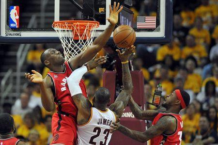 May 19, 2016; Cleveland, OH, USA; Cleveland Cavaliers forward LeBron James (23) shoots the ball as Toronto Raptors center Bismack Biyombo (8) and forward Terrence Ross (31) defend during the second quarter in game two of the Eastern conference finals of the NBA Playoffs at Quicken Loans Arena. Mandatory Credit: Ken Blaze-USA TODAY Sports