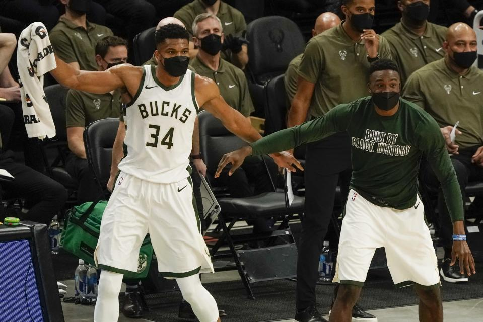 Milwaukee Bucks' Giannis Antetokounmpo and Thanasis Antetokounmpo reacts after teammate Donte DiVincenzo made a three-point basket during the first half of an NBA basketball game against the Minnesota TimberwolvesTuesday, Feb. 23, 2021, in Milwaukee. (AP Photo/Morry Gash)
