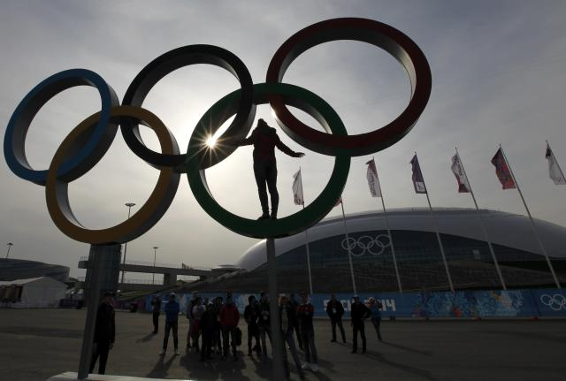 A woman stands in a set of Olympics rings as she has her picture taken at the Olympic Park a day after the closing ceremony for the 2014 Sochi Winter Olympics, February 24, 2014. REUTERS/Gary Hershorn (RUSSIA - Tags: SPORT OLYMPICS)