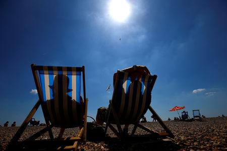 FILE PHOTO: Visitors relax on deckchairs in the sunshine on the beach by Brighton Pier in Brighton