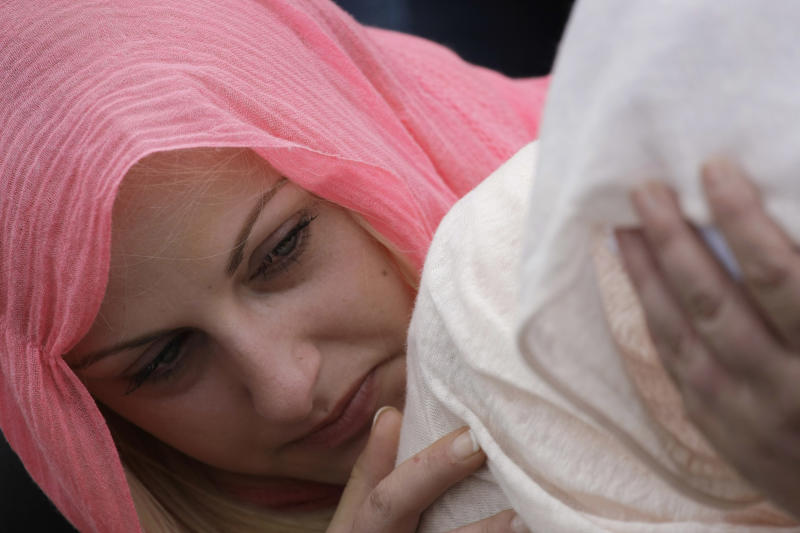 Bosnian Muslim woman Caklovica Emina, left, comforts her mother Mumina, right, near coffin of her brother during a mass funeral in the eastern Bosnian town of Kalesija, 120 kms northeast of Sarajevo, on Saturday, June 2, 2012. Thousands have gathered in the eastern Bosnian town of Kalesija to bury the remains of 32 Muslim Bosniaks killed at the start of the country's 1992-95 war. The victims' remains were discovered in numerous mass graves and they were identified through DNA analysis. (AP Photo/Amel Emric)