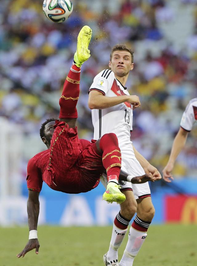 Ghana's Sulley Muntari clears the ball from Germany's Thomas Mueller during the group G World Cup soccer match at the Arena Castelao in Fortaleza, Brazil, Saturday, June 21, 2014. (AP Photo/Matthias Schrader)