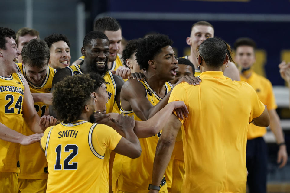 The Michigan bench congratulates head coach Juwan Howard, front right, after winning the Big Ten title against Michigan State in the second half of an NCAA college basketball game, Thursday, March 4, 2021, in Ann Arbor, Mich. (AP Photo/Carlos Osorio)