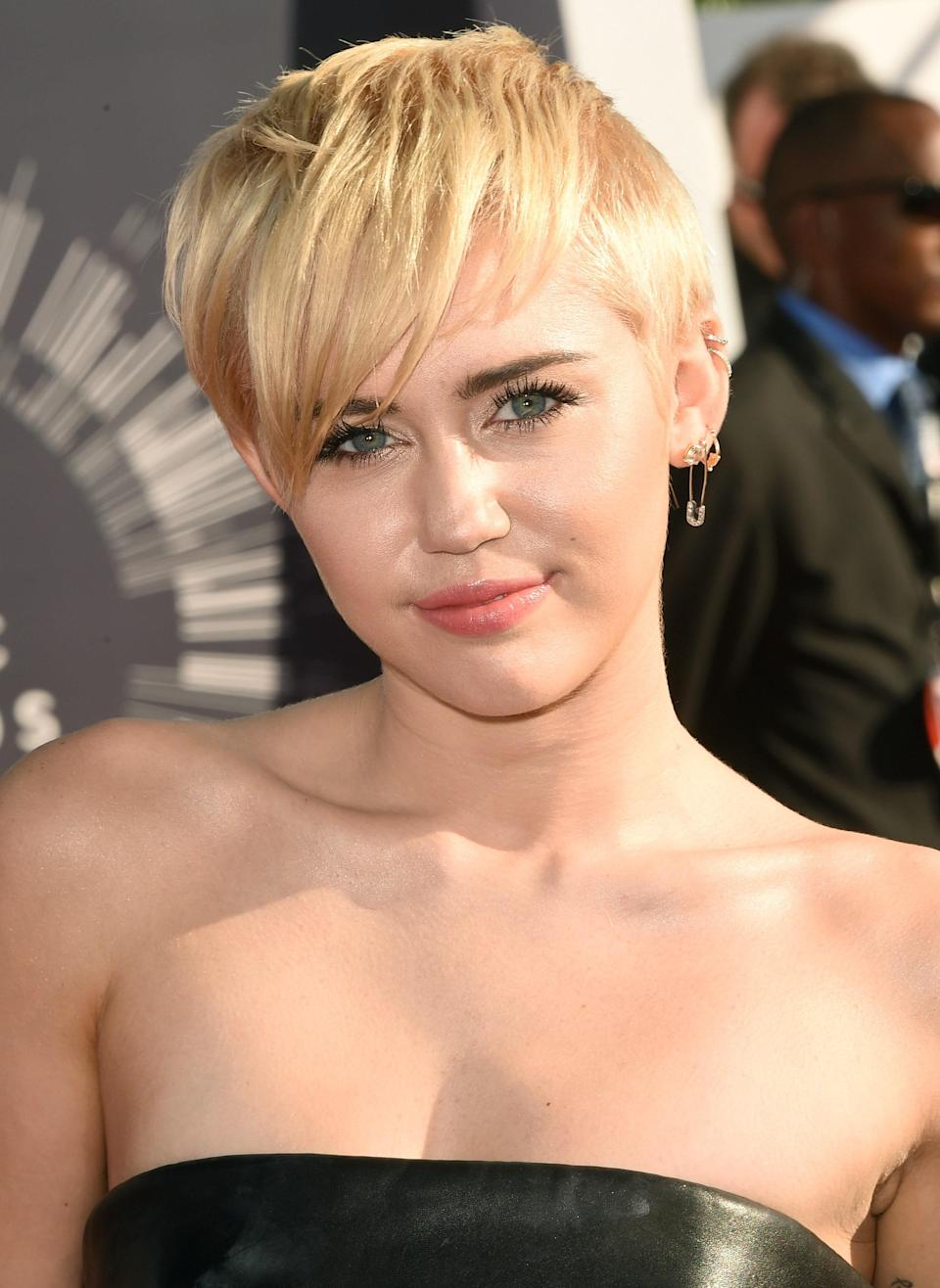 Just one year before hosting the 2015 ceremony with fluorescent lashes and neon hair, Miley showed off her softer side with a sleek short 'do and no-makeup makeup.