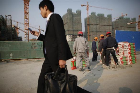 A man walks past workers in the construction site of residential buildings in Shanghai November 12, 2011.